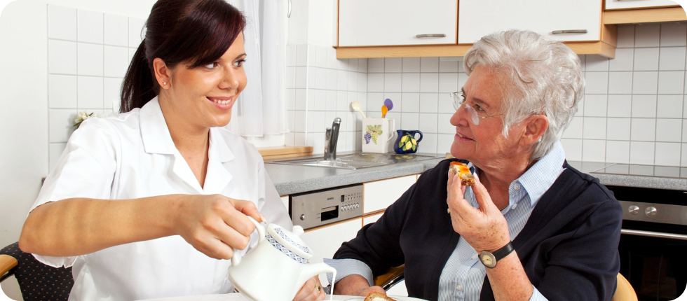 A caregiver pouring milk to cup while talking to an elderly